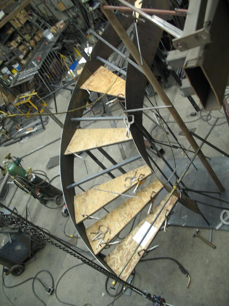 41-0060iron-anvil-stairs-grand-circular-treads-concrete-13415-ferran-kilgore-1